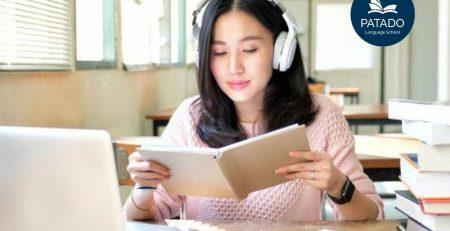 Cô gái đang tự học tiếng anh bên cạnh laptop